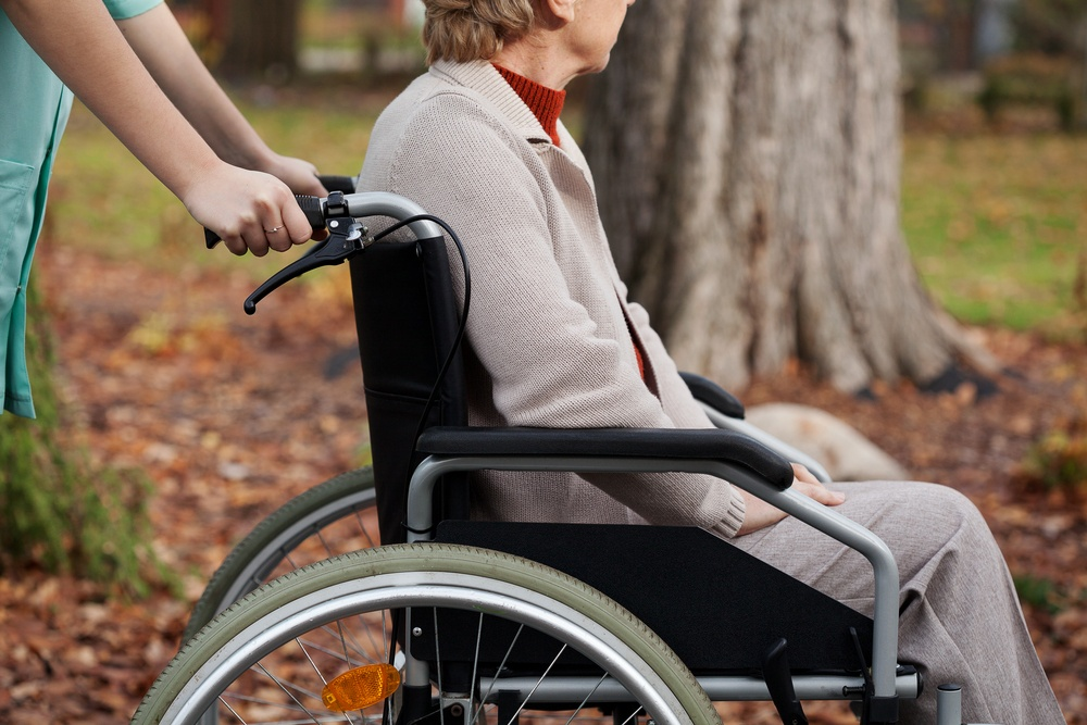 Disabled elder woman on wheelchair with nurse.