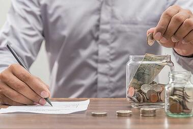 Man putting coin into change jar and writing amount on piece of paper