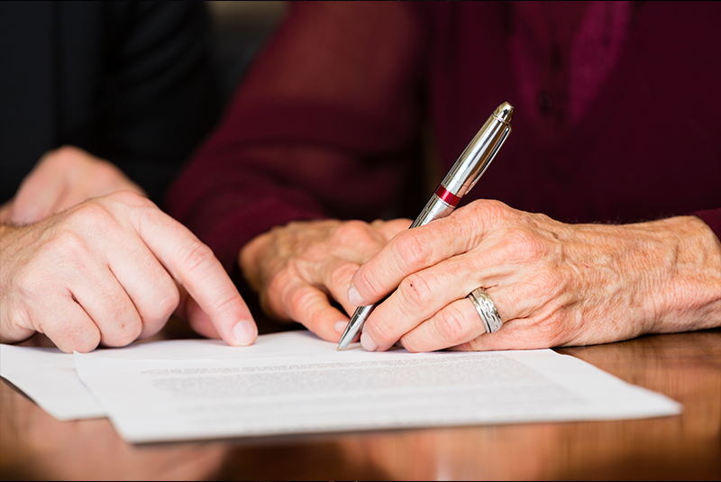 senior-signing-paper-contract-document-with-younger-hand-pointing