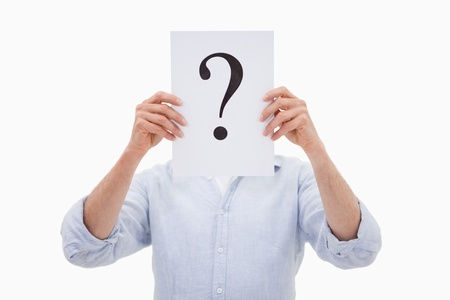man hiding his face behind a question mark against a white background